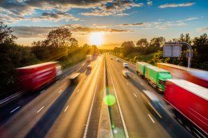 Blick von oben auf die Autobahn A% mit zahlreichen Autos und LKWs bei Sonnenuntergang