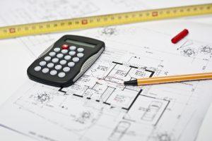 Ein Taschenrechner, eine Stift und ein Messband liegen auf einem Bebauungsplan