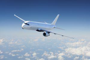 Ein weißes Flugzeug fliegt bei blauem Himmel über den Wolken