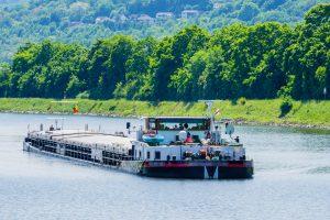 Ein mittelgroßes Frachtschiff fährt über den Rhein bei Kehl