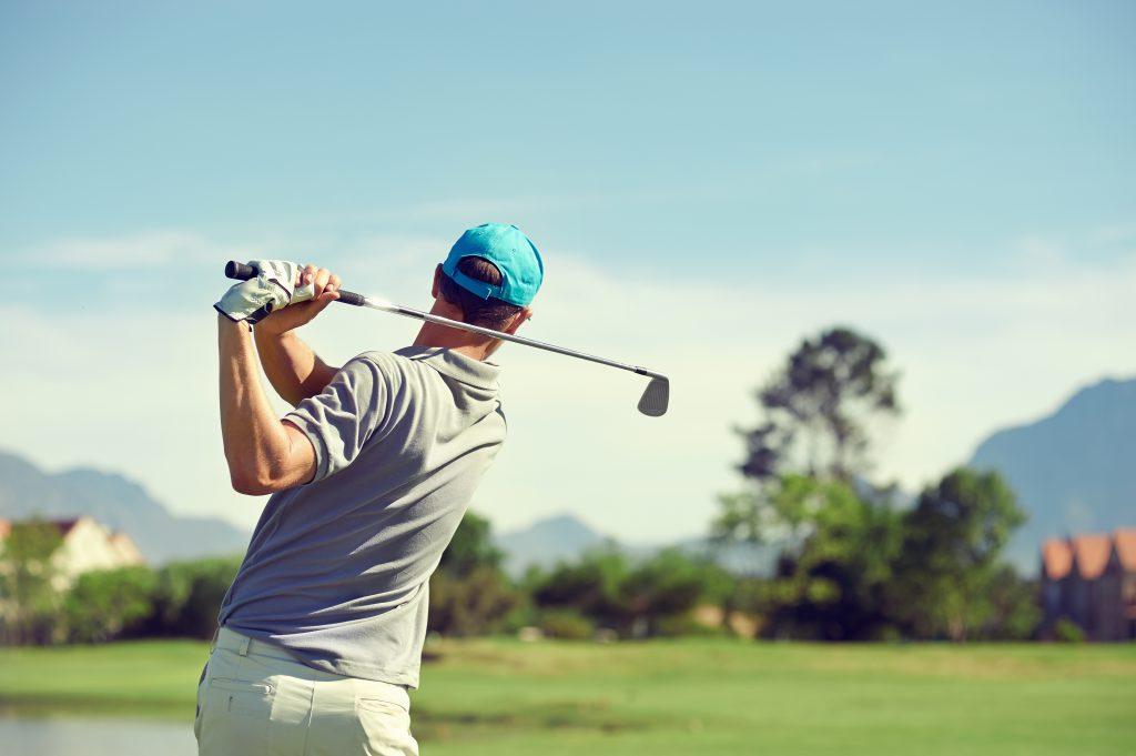 Ein Mann mit Golfkleidung hält einen Golfschläger in der Hand und befindet sich auf einer Golfanlage
