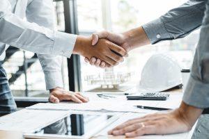 Zwei Menschen stützen sich mit jeweils einer Hand auf den Tisch und jeweils mit der anderen Hand schlagen Sie zur Zusammenarbeit ein