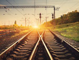 Blick auf unbefahrene Schienen mit dem Beginn eines Sonnenuntergangs