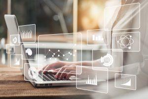 Ein Hintergrundausschnitt eines Laptops mit Mitarbeiter wird überzeichnet von digitalen Grafikauswertungen