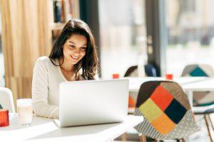 Eine Frau sitzt an einem Tisch und schaut auf ihren Laptop